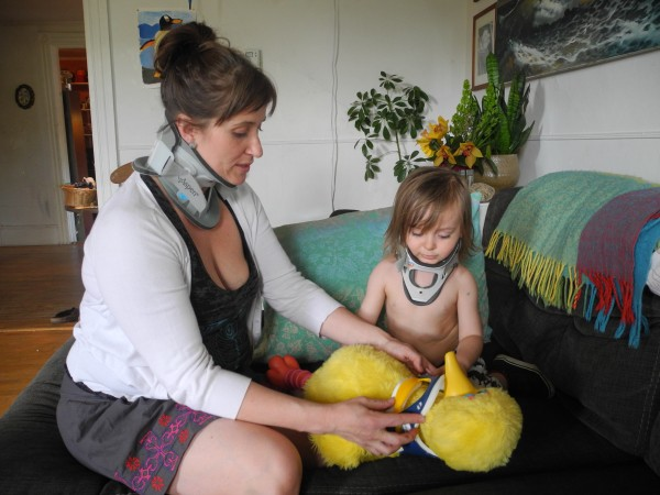 Isis Bell-Smith watches as her son, Felix Bell-Smith Laracy, puts a neck brace on his Big Bird doll on Friday in Orono. The two each broke their necks when a tree branch crashed onto their Jeep on May 4.