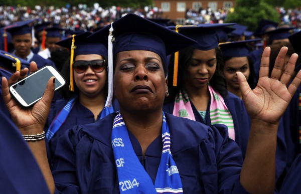 A graduate cries during a prayer at the 2014 graduation ceremonies at Howard University in Washington on May 10, 2014. Entertainer Sean Combs delivered the commencement address and received an honorary degree in Humanities during the ceremony.  A recent study reveals that skipping college could cost a person $800,000 over a lifetime.