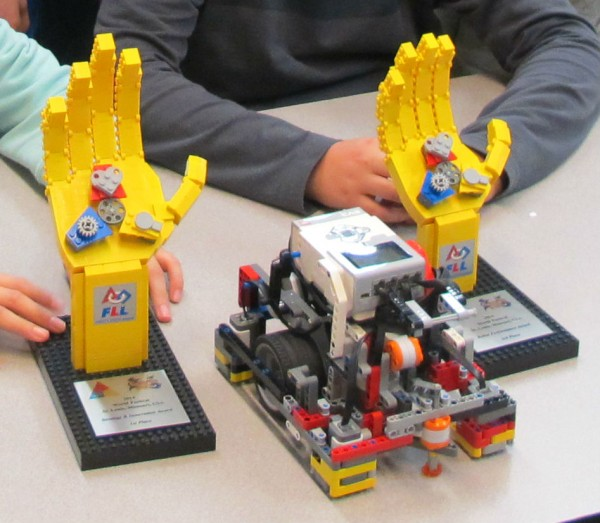 A wheeled robot used by middle schoolers on a Lego robotics team from Conners Emerson School in Bar Harbor sits in between two trophies the team recently won at an international Lego robotics competition in St. Louise, Missouri.