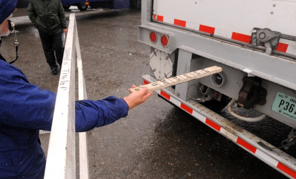 A judge checks the distance between the back of a trailer and an obstacle during the 2014 Maine Professional Driving Championships at Dysart's in Hermon on Saturday.
