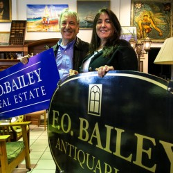 David Jones and Nancy McInnis-Jones display new signs for their side-by-side businesses on U.S. Route 1 in Falmouth. The couple of 30 years recently purchased the name F.O. Bailey, which they've added to their existing real estate and antiques businesses.