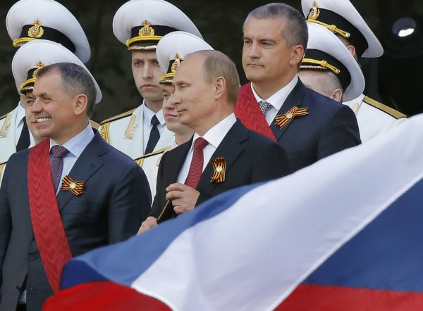 Russian President Vladimir Putin (center) makes a speech next to Crimean parliamentary speaker Vladimir Konstantinov (left), Crimean Prime Minister Sergei Aksyonov (right) and other top officials during events marking Victory Day in Sevastopol on Friday.