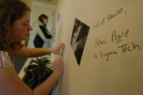 In this April 2007 file photo, UMaine student Stephanie Cummings signs a prayer wall that was set up at the university's Drummond chapel to remember victims of the Virginia Tech University shootings.