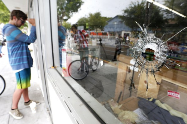 A man looks through a window with bullet holes at a deli that was one of nine crime scenes after series of drive-by shootings that left seven dead in the Isla Vista section of Santa Barbara May 24, 2014.