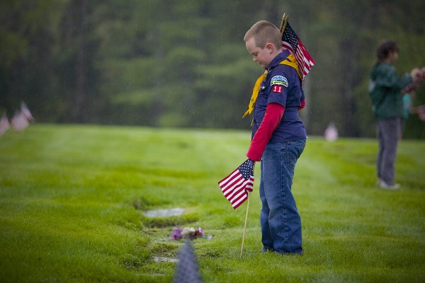 Cub Scout Dominic Tower, 8, of Pack 11 Den 2 places a flag on a grave at Woodlawn Memorial Park Cemetery on Monday afternoon in Brewer in preparation for Memorial Day.