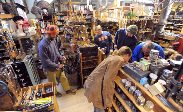 Customers and employees go through new boxes of tools Saturday morning at Liberty Tool Co.