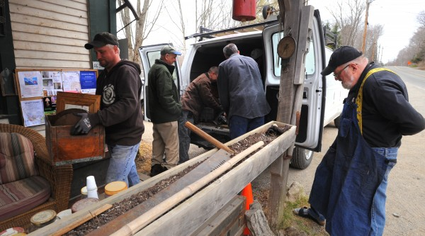 Skip Brack (right) stands back and lets his customers and employees unload tools from his van Saturday morning in Liberty.