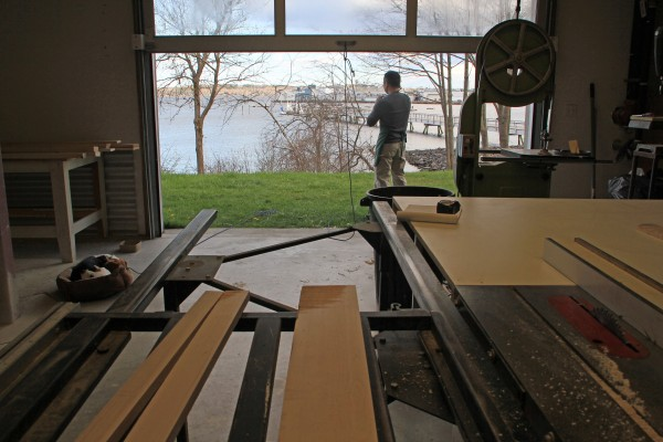 Woodworker Tom Weis speaks with a client in his shop on the lower floor of The Steel House while his dog, Clover, takes a nap nearby.