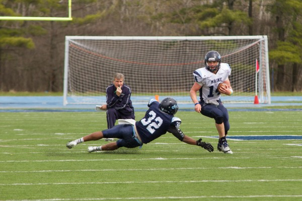 Head coach Jack Cosgrove  watches as sophomore Daniel Collins attempts to avoid being tackled during the annual Jeff Cole scrimmage Saturday morning at Morse Field at the University of Maine.