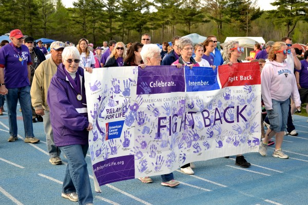 Cancer survivors take the first lap in the Relay for Life of Penobscot County during the event's 21st year Friday at the University of Maine track at Morse Field. More than 600 people participated in the event, which continued through Saturday.