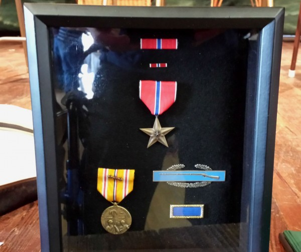 Richard Alley's long-awaited World War II military service medals, including a Bronze Star, are displayed Friday in a case sitting on a stage at the Neighborhood House on Little Cranberry Island.