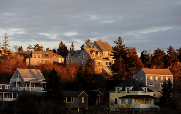 Sunset  casts its warm light on the homes of Monhegan.