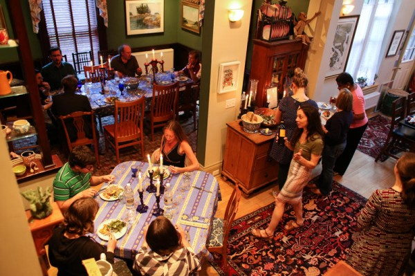 Guests take their seats for a salmon dinner at Tophat Toy Theater in a West End home in Portland.