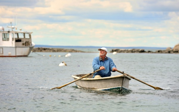 Shermie Stanley, 66, rows out to his lobster boat for a day of cleaning and repairs.