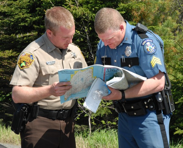 Multiple agencies are involved in the manhunt for St. Francis resident Jesse Marquis who is wanted in connection with a fatal shooting in that town early Saturday morning. Aroostook County Deputy Sheriff Kris Malmborg goes over a map of the area with Trooper Chad Fuller of the Maine State Police.