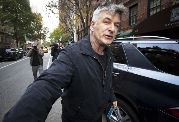Actor Alec Baldwin shoves a photographer and tells him to move out of his way after he arrived in his SUV at the building where he lives in New York in this file photo from November 15, 2013. Baldwin was arrested in New York May 13, 2014 for riding his bicycle in the wrong direction on a one-way street and acting &quotin a violent, threatening manner&quot toward police officers, officials said.