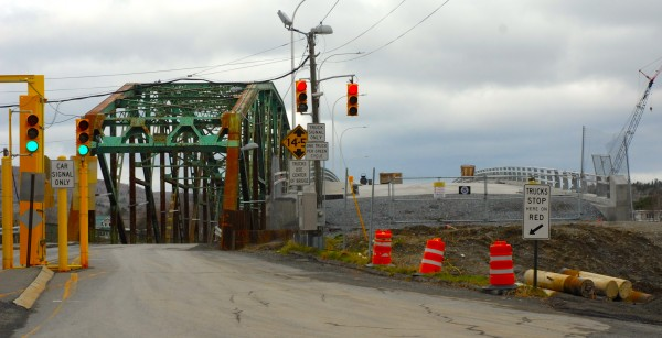 Lights direct truck and car traffic on and off the existing international bridge in Fort Kent leading into New Brunswick. Several feet to the right, construction continues on its replacement.