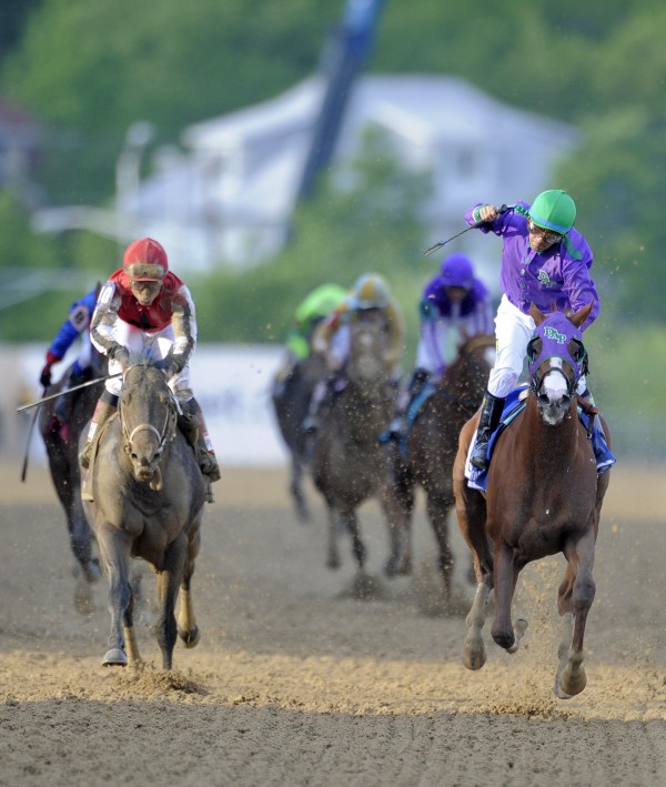 California Chrome, right, crosses the finish line to win the 139th Preakness Stakes at Pilmico Race Course in Baltimore on Saturday, May 17, 2014.