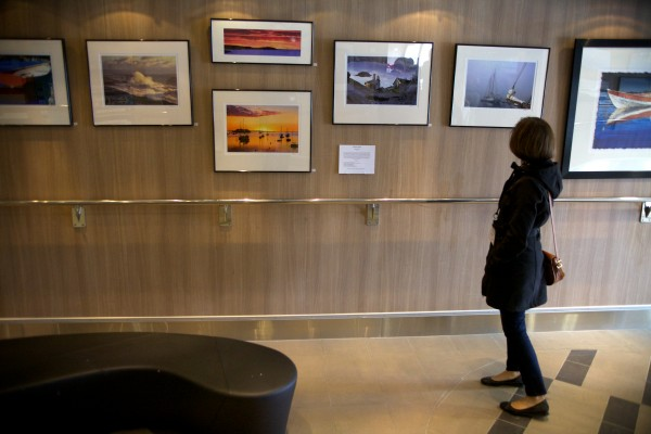 A woman gazes at works by local artists aboard the Nova Star cruise ship in Portland on Friday. The ship will offer public tours on Saturday.