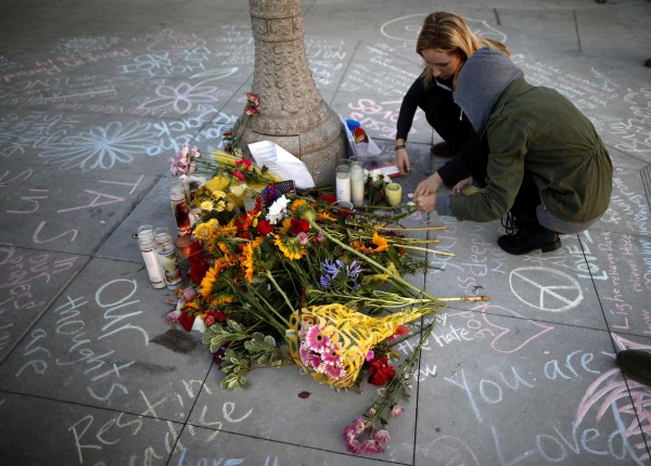 Students light candles at a tribute for victims, at one of nine crime scenes after a series of drive-by shootings that left 7 people dead, in the Isla Vista neighborhood of Santa Barbara, California May 26, 2014. Twenty-two year old Elliot Rodger killed six people before taking his own life in a rampage through the California college town.