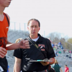 Brewer High School coach Glendon Rand watches a member of the Witches track team during a Monday meet at Cameron Stadium in Bangor.