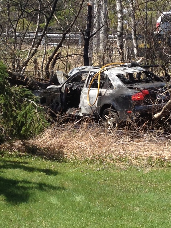 A wrecked sedan sits in the trees off Route 202 in Hampden after firefighters extinguished a blaze following an accident Wednesday.