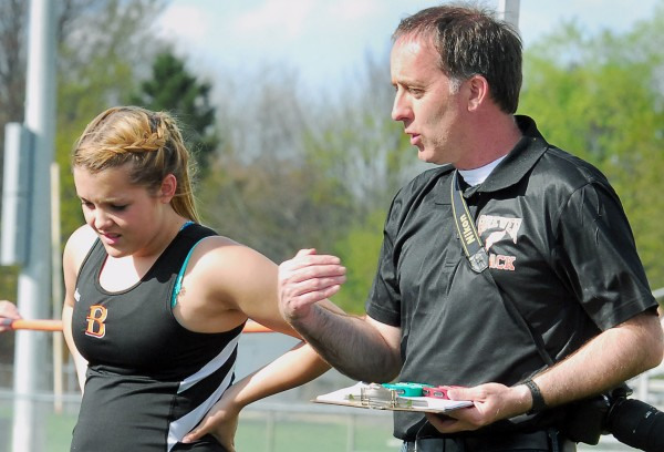 Brewer High School outdoor track and field coach Glendon Rand talks with team member Rachel Howland after a high jump during a Monday track meet at Cameron Stadium in Bangor.
