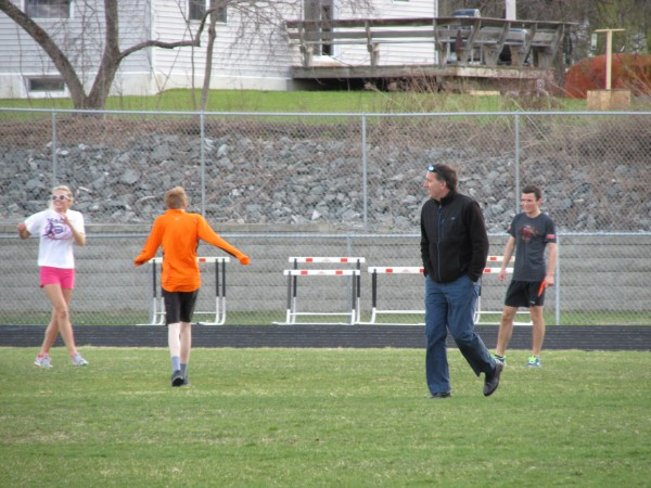 Brewer High School outdoor track and field coach Glendon Rand strolls across the infield at the Brewer Community School track during a recent team practice.