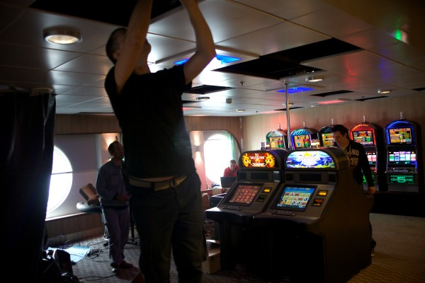 Workmen install slot machines aboard the Nova Star on Friday in Portland. The cruise ship will start making daily runs to Nova Scotia next week.