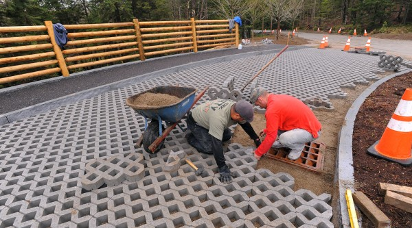 Atlantic Landscaping employees Inior Soto (left) and Steve Timbs install pavers at the Echo Lake bus stop and turning area in Acadia National Park.