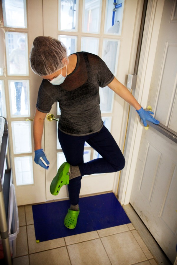 Hannah Nichols, operations manager at Mousam Valley's mushroom-growing operation in Springvale, disinfects her shoes before donning a lab coat and entering the climate-controlled growing rooms to harvest fungi on Monday.