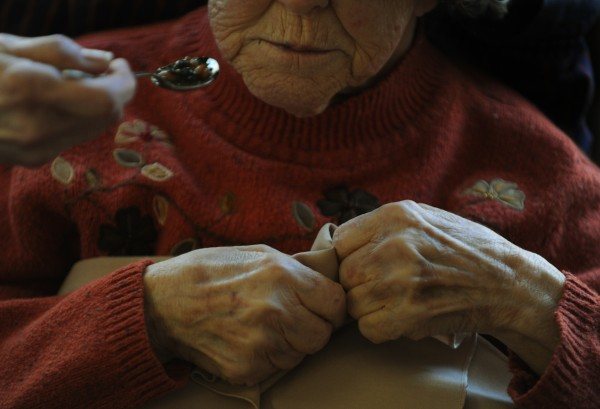 A woman clutches her napkins as her daughter feeds her bean soup at the Orono Commons nursing home in this Thursday, Jan 26, 2012, file photo.