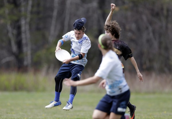 A Middletown High School player loses his hat while making a jumping catch against a Cape Elizabeth player on Saturday in South Portland.