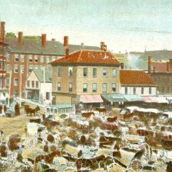 A large lunch wagon can be seen stationed behind other wagons selling farm produce in Pickering Square in this turn-of-the-century postcard showing Bangor's big open-air market.