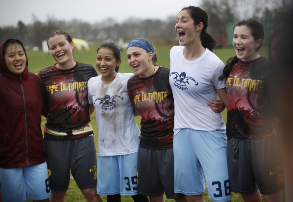 Cape Elizabeth players, wearing dark shirts, and Lexington players sing a song together after their game in the rain on Saturday in South Portland.