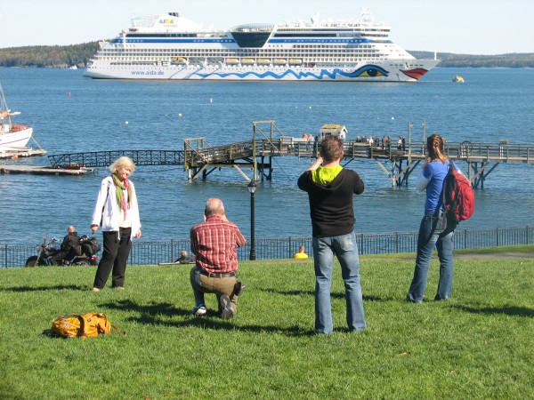 Tourists in Bar Harbor take pictures of the cruise ship AIDA Bella anchored offshore on in October 2013.