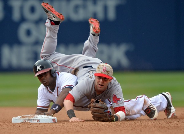 Boston Red Sox second baseman Dustin Pedroia lands on Atlanta Braves' Justin Upton during  a double play in the bottom of the sixth inning Monday, May 26, 2014 at Turner Field in Atlanta. The Red Sox beat the Braves 8-6.