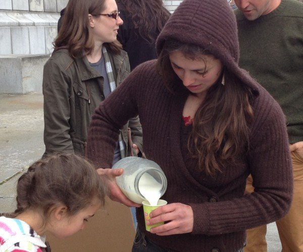Bridget McKeen of Hogback Mountain Farm in New Montville pours a small cup of raw Jersey milk for supporters of former farmer Dan Brown outside the Maine Supreme Judicial Court on Tuesday.