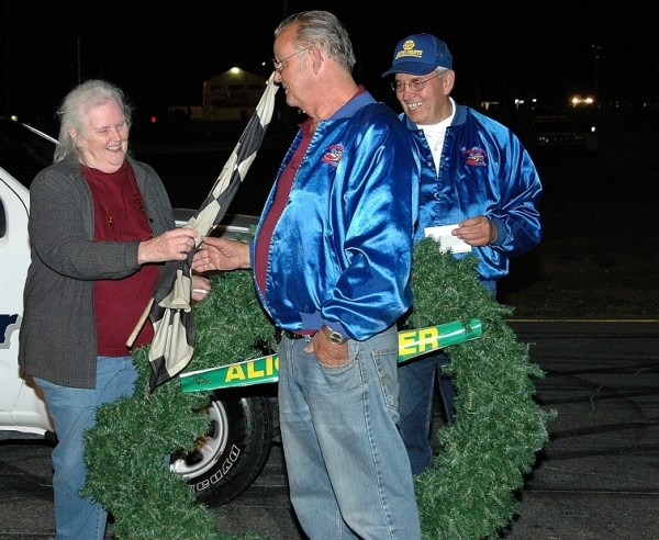In this 2011 file photo, Speedway 95 owner Del Merritt (center) participates in a retirement ceremony for former co-owner, Alice Baker, at the track in Hermon.