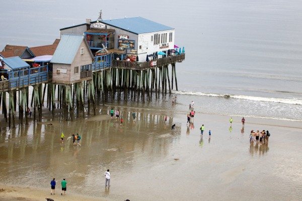 Surf-seekers tread the sand at Old Orchard Beach Monday.