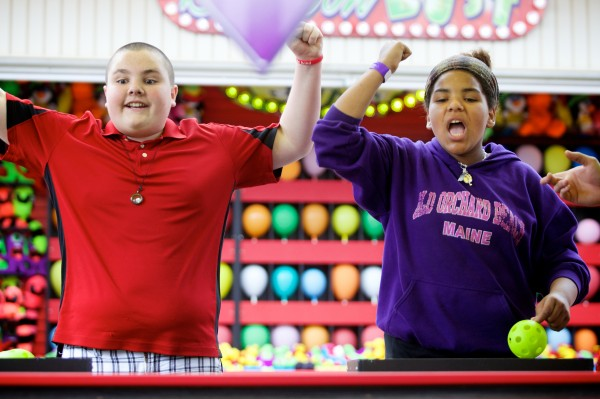 Dyllan Hinton, 12, and Maya Haley, 12, celebrate a win at a ball tossing game at Old Orchard Beach Monday.