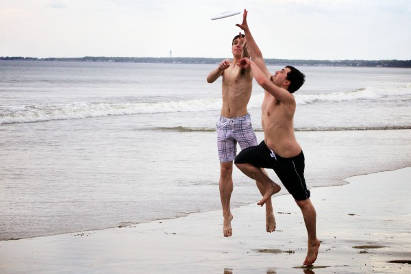 Tyler Leighton, left, and Nicj Derosier both take a stab at a flying disc on Old Orchard Beach Monday.