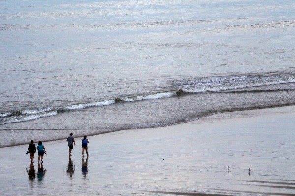Beachcombers make their way down the sand at Old Orchard Beach Monday.