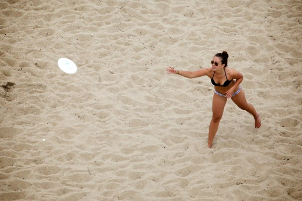 A woman tosses a flying disc on the sand at Old Orchard Beach Monday.