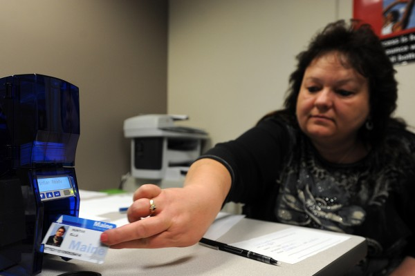 In this April 2014 file photo, Sue Sapiel, customer service representative at the Department of Health and Human Services Office of Family Independence, prints out a new EBT card that includes a photo.