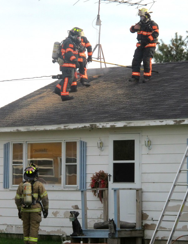 Firefighters stand on the roof of a house on Macomber Mill Road in Eastbrook on Tuesday evening. A woman who lives in the house, Nancy Rogers, suffered smoke inhalation when she went back into the house in an unsuccessful attempt to rescue her three dogs and a bird. A spokesman for Eastern Maine Medical Center in Bangor said Wednesday that Rogers remains at the hospital in critical condition.