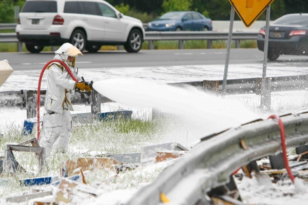 Dominic Pizzo with Station 33 Delaware Air Guard uses foam to spray on the millions of bees along I-95 near Newark, Delaware, on Wednesday.