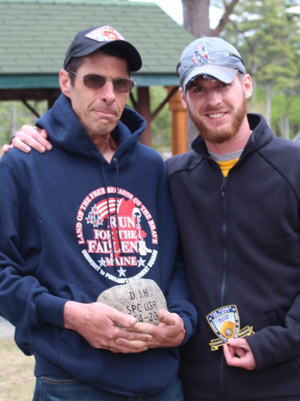 Scott Harris of Patten, holding a tribute stone for his son Army Spc. Dustin J. Harris, poses for a photo while standing with his son Dylan Harris on Saturday, during The Summit Project celebration at Twin Pine Camps near Baxter State Park. Dylan Harris carried his brother's stone to the top of The Owl, a mountain in the park, along with 35 other hikers who carried tribute stones to honor Maine's fallen heroes.