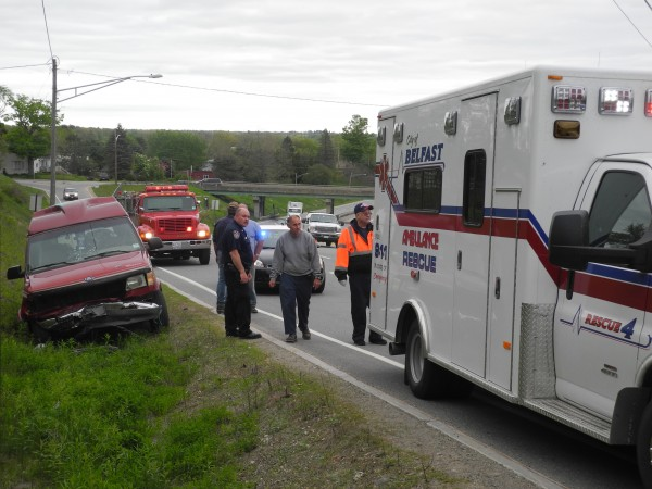 Police and rescue workers assist at the scene of a two-car collision that required the Jaws of Life to cut two people out of their vehicle.