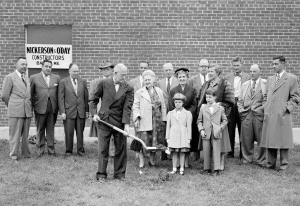 Henry J. Thibodeau, the NEWS employee with the longest active service, officially began construction of the new building at Main and Buck streets by breaking ground on Sept. 22, 1953. Thibodeau, day supervisor of the composing room, joined The NEWS on May 15, 1918. Watching the first spadeful are Carolyn, 6, and Ricky Warren, 8, front row. Second row, left to right, are Mrs. Mary A. Towle; Mrs Lillis T. Jordan, president and publisher; and Mrs. Joanne J. Warren. Third row, Andrew J. Pease, advertising manager; Raymond J. Cox, production manager; John M. O'Connell, Jr., managing editor; Frank L. Ames, general manager; Robert E. Kiah, business manager; Walter S. Lancaster, architect; Ambrose S. Higgins, architect; Leroy S. Nickerson, constructor; Gerald O'Day, constructor; and Richard K. Warren, assistant publisher.